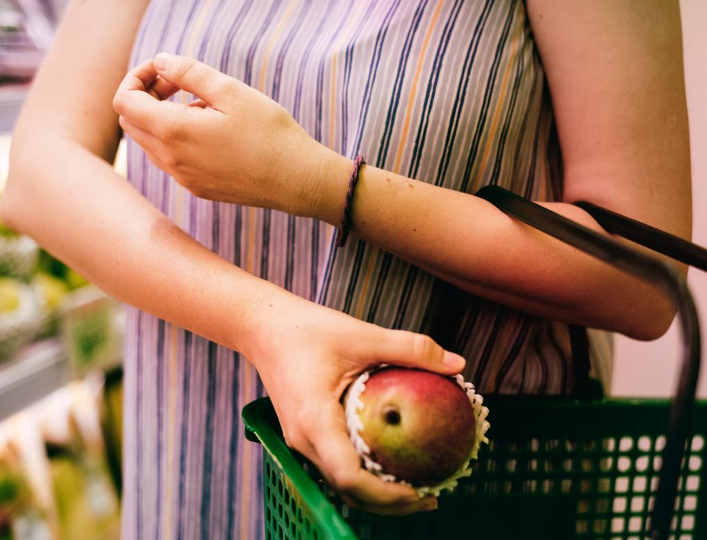 mujer sosteniendo mango cesta compra